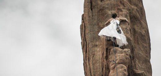 Frau im weissen Kleid hält sich beim Klettern an Fels fest